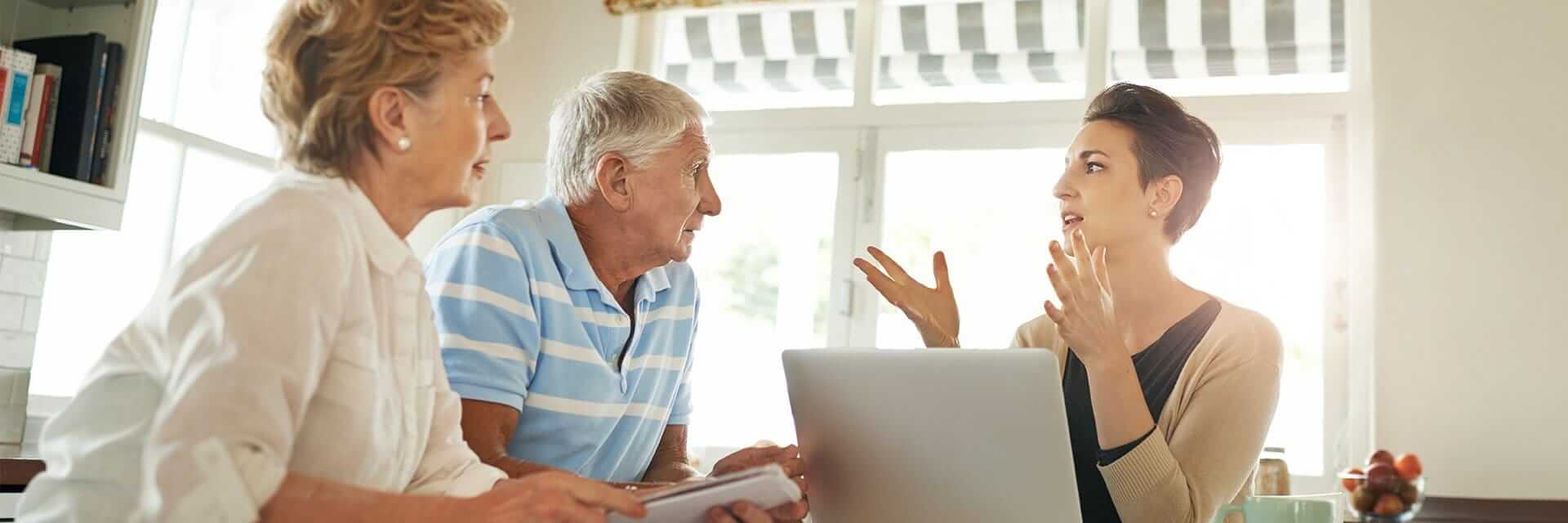 A young, female financial professional provides guidance to an elder couple.